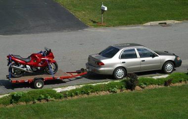 Voiture qui transporte une moto dans une remorque